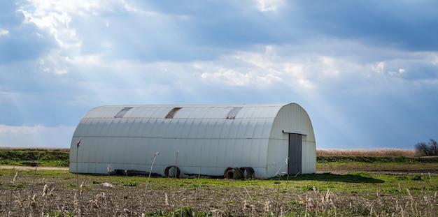 Bela vista de uma estufa branca no meio de um campo