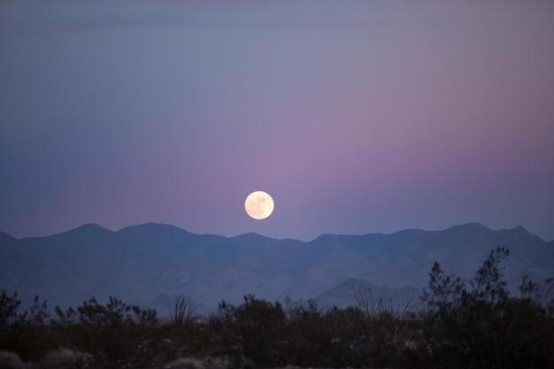 Bela vista de uma lua cheia ao anoitecer acima das silhuetas das montanhas e da vegetação