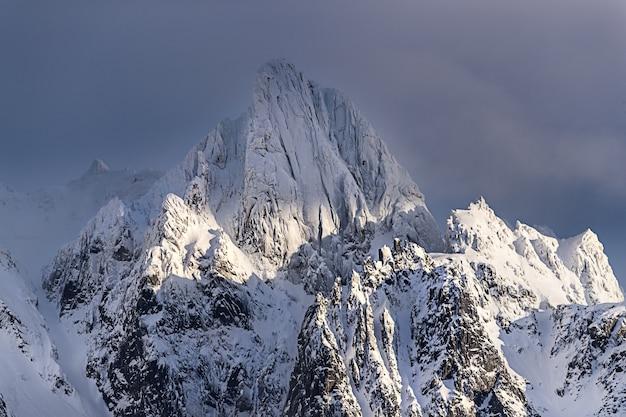 Bela vista de uma montanha incrível coberta de neve sob o céu nublado na noruega