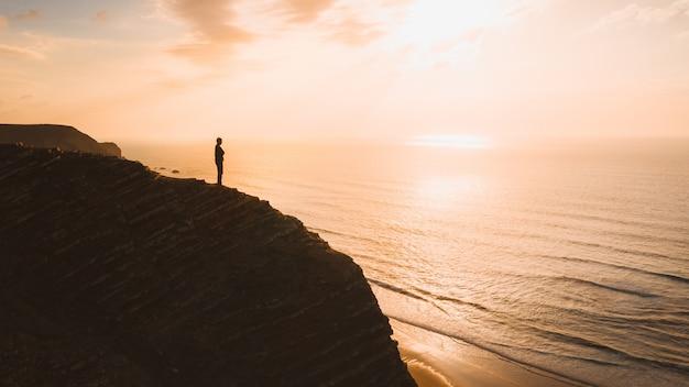 Bela vista de uma pessoa em pé em um penhasco sobre o oceano ao pôr do sol no algarve, portugal
