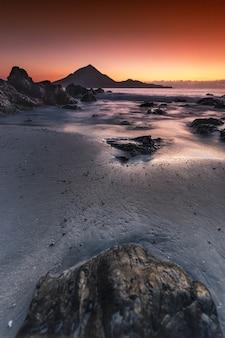 Bela vista de uma praia com momentos durante o pôr do sol