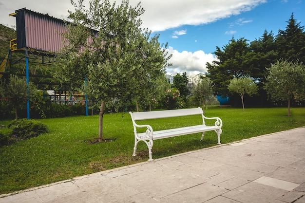Bela vista do banco branco no parque com árvores e gramado
