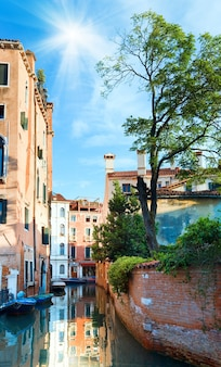 Bela vista do canal veneziano de verão com árvore, sol no céu azul e reflexos (veneza, itália)