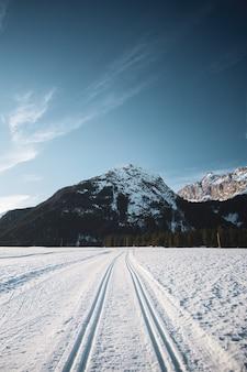 Bela vista do céu azul com montanhas e uma estrada cheia de neve com marcas de pneus durante o inverno