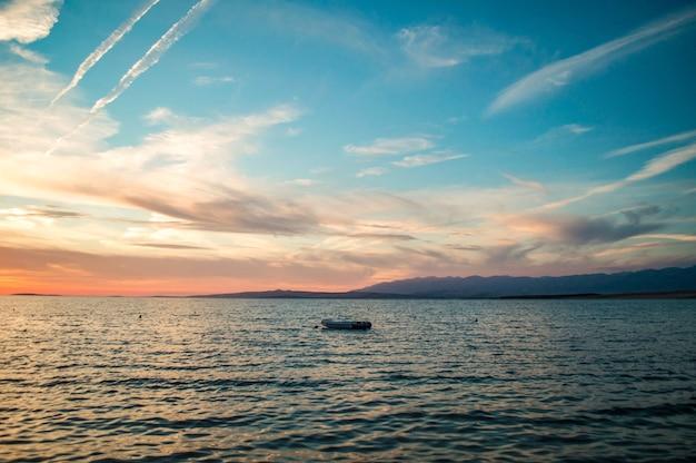 Bela vista do céu nublado no pôr do sol sobre uma paisagem marinha