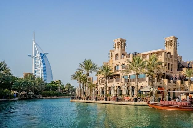 Bela vista do famoso hotel burj al arab. dhow árabe tradicional navegando na baía.