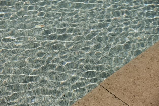 Bela vista do lado da piscina com água azul clara e reflexos da onda de sombra da luz do sol Foto Premium