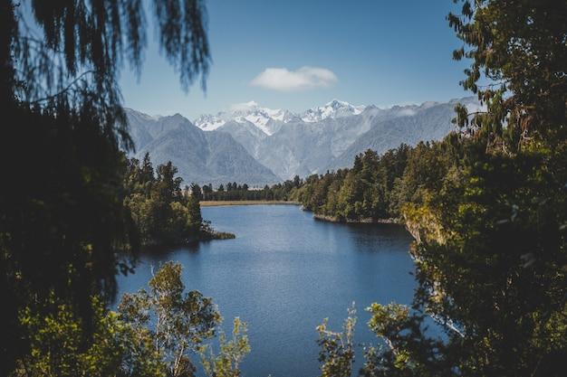 Bela vista do lago matheson na nova zelândia com um céu azul claro ao fundo