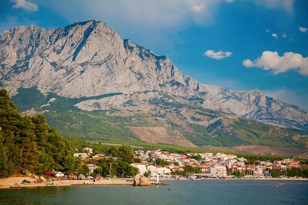 Bela vista do litoral no resort baska voda com grandes montanhas ao fundo, croácia