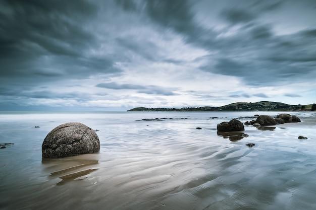 Bela vista do mar com pedras na costa e montanhas ao longe