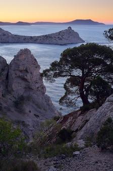 Bela vista do mar com pedras na costa. vista noturna do mar e do cabo da montanha