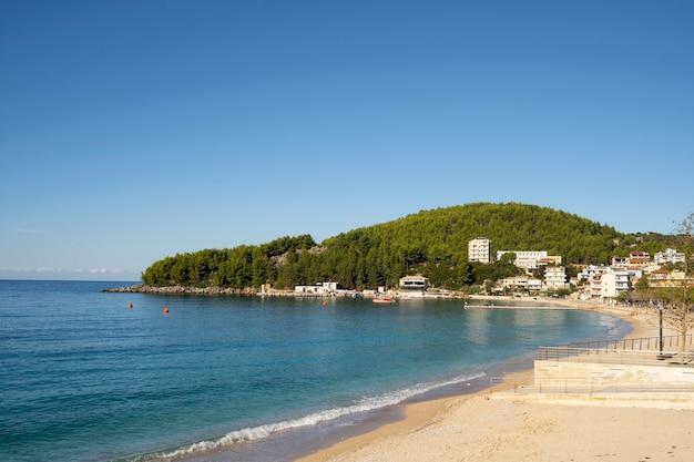 Bela vista do mar com praia de areia e península florestal