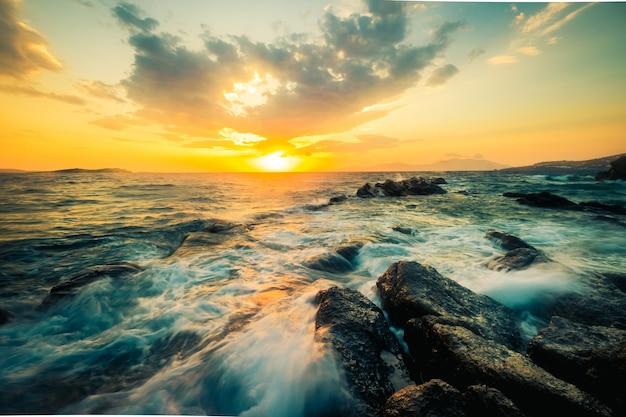 Bela vista do mar com rochas e ondas ao pôr do sol