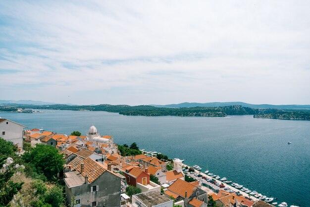 Bela vista do mar e do cais com iates por trás dos telhados de casas antigas em sibenik