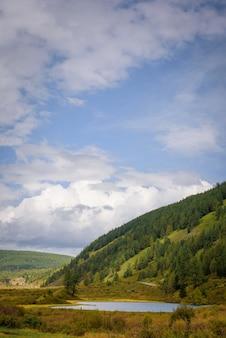 Bela vista do pequeno lago entre colinas verdes cobertas por floresta de coníferas.
