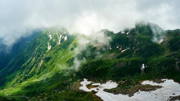 Bela vista do pico da montanha achisho, neve e céu nublado, verão em sochi, rússia