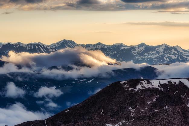 Bela vista do pôr do sol com montanhas e nuvens cobertas de neve do monte evans, no colorado