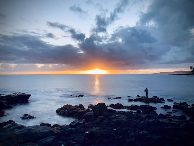 Bela vista do pôr do sol no céu nublado sobre o oceano calmo na costa rochosa