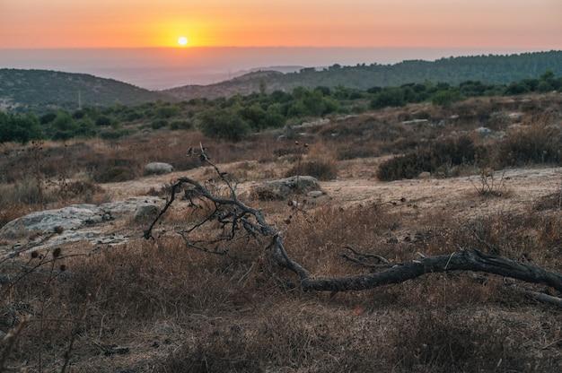 Bela vista do pôr do sol no horizonte sobre campos montanhosos