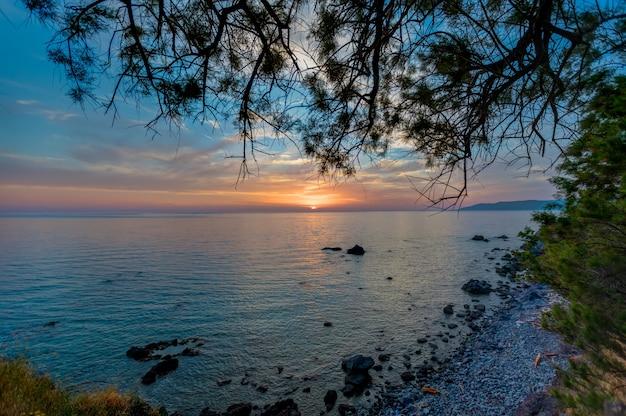 Bela vista do pôr do sol sobre o oceano calmo capturado em lesbos, grécia