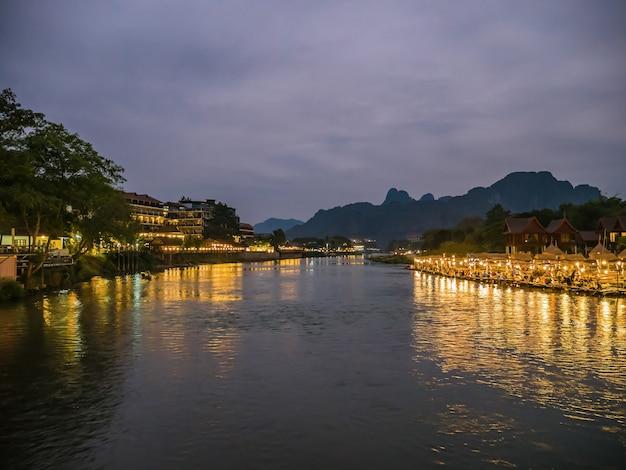 Bela vista do rio nam song com restaurante ribeirinho e a montanha à noite na cidade de vangvieng lao.