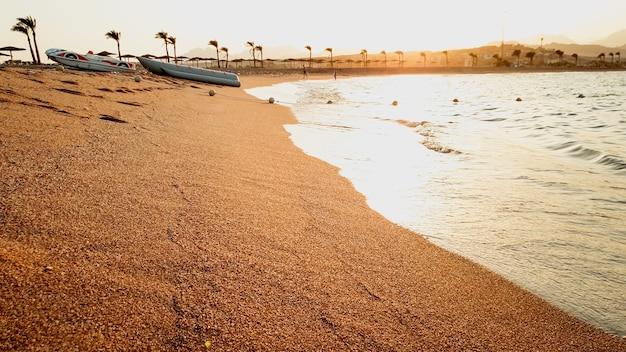 Bela vista do sol se pondo sobre o mar. bela praia de areia e ondas rolando na costa