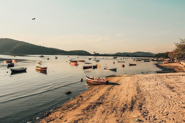 Bela vista dos barcos de pesca no mar perto de uma costa arenosa