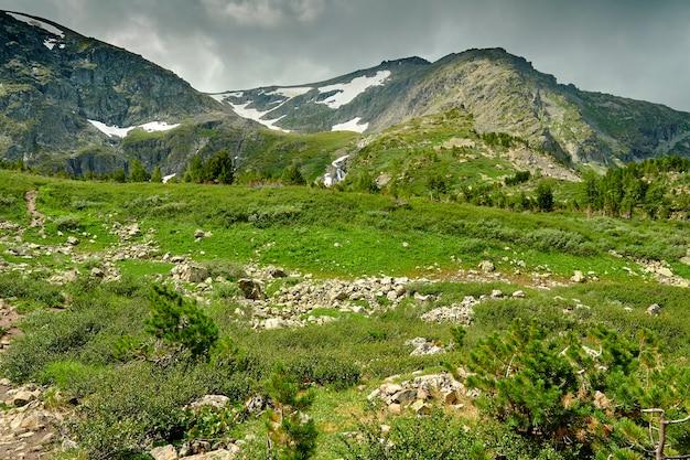Bela vista dos picos das montanhas cobertos de neve. prados verdes alpinos contra o pano de fundo dos picos das montanhas cobertas de neve. paisagem montanhosa