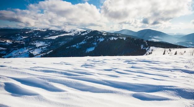 Bela vista fascinante das encostas das montanhas com densas árvores e montes de neve contra o céu e nuvens brancas em um dia frio de inverno