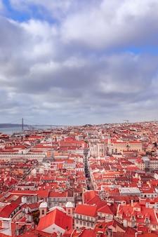 Bela vista panorâmica da cidade de lisboa com telhados vermelhos sob um céu nublado.