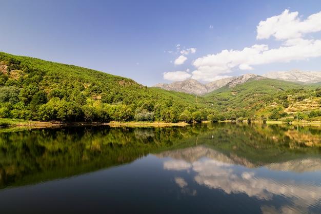 Bela vista panorâmica de um lago cercado por montanhas verdes