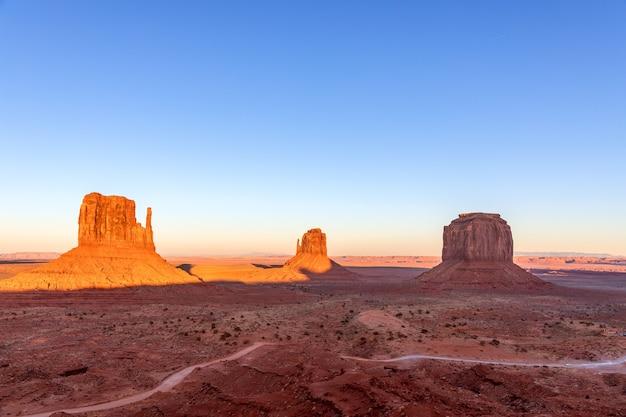 Bela vista panorâmica do pôr do sol sobre os famosos montes de monument valley, na fronteira entre o arizona e utah, eua