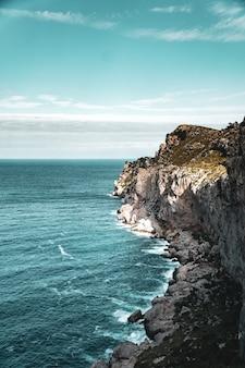 Bela vista vertical da costa rochosa e do mar azul e calmo