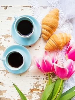 Bela xícara de café, croissants e tulipas cor de rosa na mesa branca velha