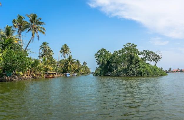 Belas águas da paisagem indiana em kerala, com palmeiras, céu azul e águas azul-turquesa. canais na veneza indiana de alleppey.