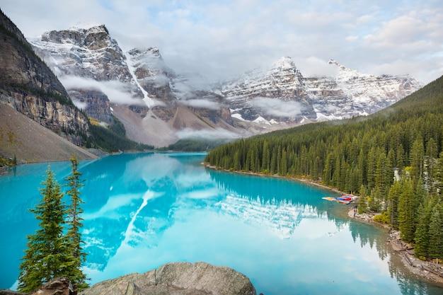 Belas águas turquesa do lago moraine com picos cobertos de neve no parque nacional de banff do canadá