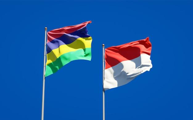 Belas bandeiras de estados nacionais da maurícia e da indonésia juntas no céu azul