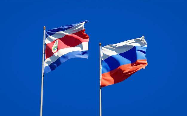 Belas bandeiras do estado nacional da rússia e da costa rica juntos no céu azul. arte 3d