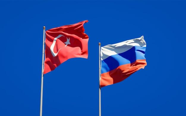 Belas bandeiras do estado nacional da turquia e da rússia juntos no céu azul. arte 3d