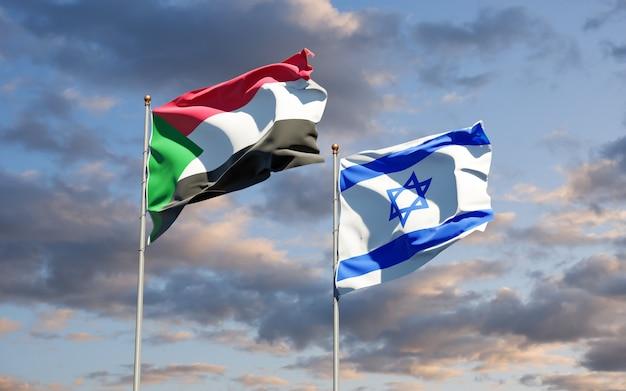 Belas bandeiras do estado nacional de israel e sudão juntos ao fundo do céu.