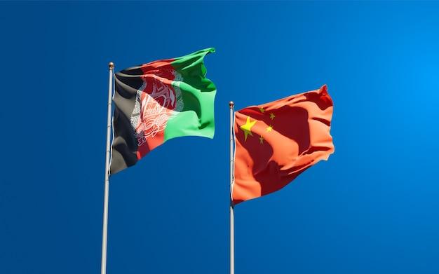 Belas bandeiras do estado nacional do afeganistão e da china juntos no céu. conceito de arte 3d.