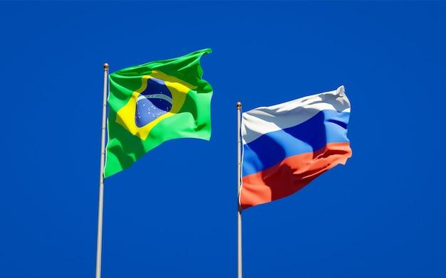 Belas bandeiras do estado nacional do brasil e da rússia juntos no céu azul. arte 3d