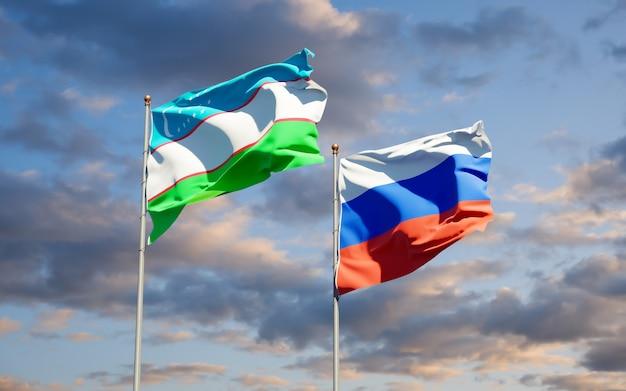 Belas bandeiras do estado nacional do uzbequistão e da rússia juntos no céu azul. arte 3d