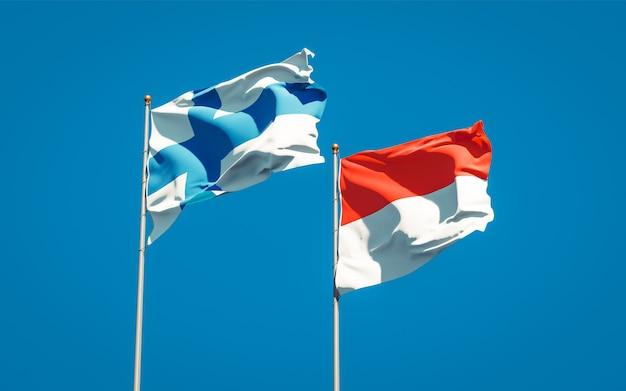 Belas bandeiras estaduais da finlândia e da indonésia juntas no céu azul