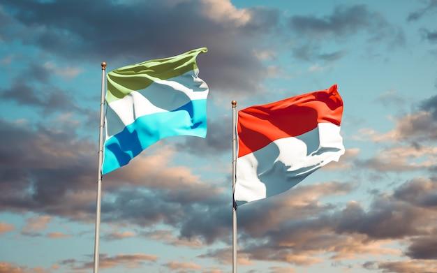 Belas bandeiras estaduais de serra leoa e indonésia juntas no céu azul