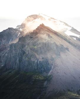Belas colinas íngremes e montanhas nevadas com o céu incrível