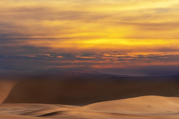 Belas dunas de areia dourada e céu dramático com nuvens brilhantes no deserto do namibe