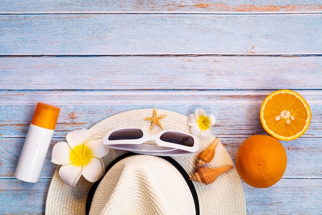 Belas férias de verão, acessórios de praia, óculos de sol, chapéu, protetor solar e laranja