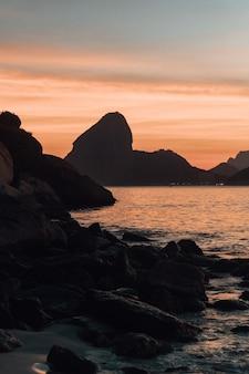 Belas formações rochosas perto do mar com o pôr do sol no rio de janeiro