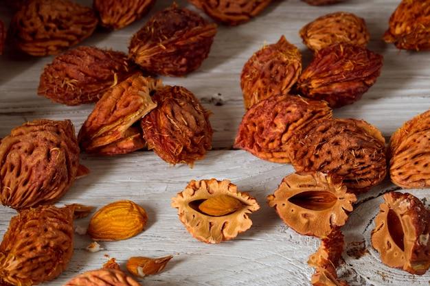 Belas frutas de pêssego e muitos caroços de pêssego em fundo de madeira